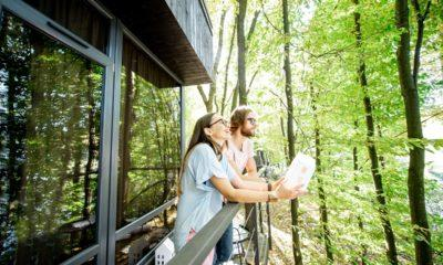 Couple with house model on the balcony in the forest